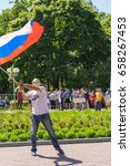 """Small photo of A masked man and a flag at a rally at a rally against corruption in the city of Cheboksary, the Chuvash Republic. Russia. 06/12/2017 The inscription on the T-shirt """"I'm sick of myself"""""""
