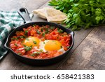 shakshuka in iron frying pan on ... | Shutterstock . vector #658421383