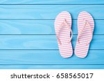 pink flip flops on blue wooden... | Shutterstock . vector #658565017