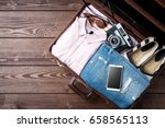 open suitcase with casual... | Shutterstock . vector #658565113