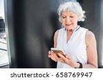 cheery elderly lady texting... | Shutterstock . vector #658769947