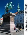 Small photo of Copenhagen, Denmark - April 30, 2017: Girl sitting under the equestrian statue of Absalon on High Bridge Square or Hojbro Plads