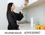 Small photo of Young woman in the kitchen opening ambry in bathrobe in the morning