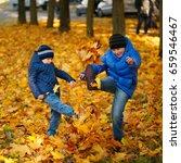 two boys kick maple leaves in... | Shutterstock . vector #659546467
