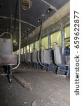 Small photo of Chipped and peeling seats and aisle of abandoned trolley car.