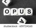 Small photo of word opus on white toy cubes