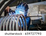 worker is welding metal tubes. | Shutterstock . vector #659727793