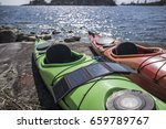 Small photo of Portable solar panels lie on the kayak that stand on the shore of the lake and accumulate energy.
