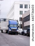 Small photo of A blue modern semi truck with high roof to reduce air resistance and improve aerodynamics carries dry van trailer with cargo along the road in an urban city street