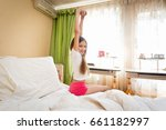 Small photo of Smiling teenage girl stretching hands after wakening at morning