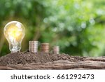 Small photo of Light bulb and money on the ground at green Natural background. Natural energy and Costs reduction concept