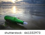 Small photo of Message in a bottle on beach during sunset