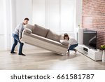 young happy couple placing sofa ... | Shutterstock . vector #661581787