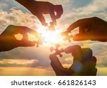Small photo of Collaborate four hands trying to connect a puzzle piece with a sunset background. A puzzle in hand against sunlight. One part of the whole. Symbol of association and communication. Business strategy.