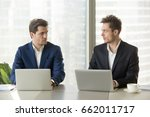 Small photo of Two confident businessmen sitting at office desk with laptops, looking at each other with hate dislike, rivals accepting challenge, business competition, team rivalry at work, competitors behavior