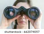 Small photo of Girl looking through the binoculars. Find and search concept.