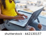 Small photo of Cropped image of young woman holding a laptop on lap typing keyboard indoors in public place