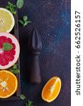 Small photo of Orange, lemon and grapefruit with citrus reamer on dark table background