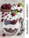 Small photo of Trifle dessert with brownie, cream cheese frosting and raspberry in a glass, vertical