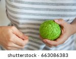 The Girl Is Holding A Ball Of...