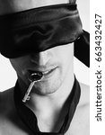 Small photo of A man with a blindfold is holding a key in his teeth