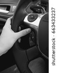 Small photo of Closeup black and white photo of female driver adjusting cruise control system on steering wheel