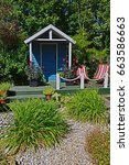 Small photo of Summer House with decking, flower containers with Dahlias and seating