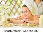 girl lying down on a massage bed | Shutterstock . vector #664255387