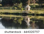 Small photo of A friendly looking gazebo sits beside a public pond inviting one to come and sit for awhile.