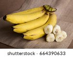 banana and a sliced banana on ... | Shutterstock . vector #664390633
