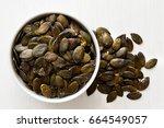 hulled pumpkin seeds  in white... | Shutterstock . vector #664549057