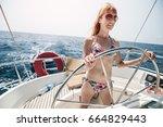 young woman in bikini steering... | Shutterstock . vector #664829443