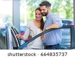 young couple buying a car  | Shutterstock . vector #664835737
