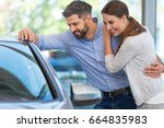 young couple buying a car  | Shutterstock . vector #664835983