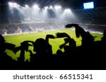 Silhouettes of fans celebrating a goal on football / soccer match - stock photo