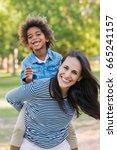 smiling mom giving to her black ... | Shutterstock . vector #665241157