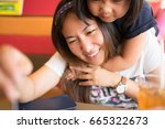 Small photo of Happy mother's day! Child daughter congratulates mom and gives her cake and postcard. Mum and girl smiling and hugging in restaurant.Family holiday and togetherness.