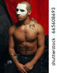 Small photo of Medieval painting concept. Arty portrait of circus performer in black tights with sequins on body. Italian white mask make-up on face. Muscular body and perfect tan