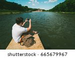 Man sitting on a lake pier and taking picture on the phone in sunny summer day