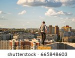 a lone roofer walks along the... | Shutterstock . vector #665848603