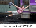 Stock photo man with backpack flies behind a moving train tourist holding a moving train from a railway 665871163