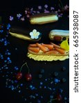 Small photo of Different eclair dessert on dark wooden table decorated with strawberries and flowers