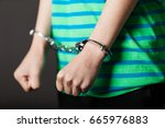 Close up on pair of hands from child or teenager in green and blue shirt tied with metal handcuffs