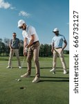 young golfer putting ball into... | Shutterstock . vector #666732127