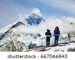 Small photo of Panoramic view of Mount Everest from Kala Patthar with two tourists on the way to Everest base camp, Sagarmatha national park, Khumbu valley - Nepal