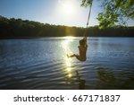boy bungee jumping over water.... | Shutterstock . vector #667171837