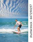man learning to surf on the... | Shutterstock . vector #667250257