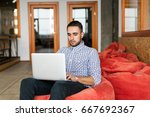 serious man working on laptop... | Shutterstock . vector #667692367