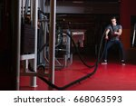 battling ropes man at gym... | Shutterstock . vector #668063593