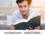 handsome man reading a book... | Shutterstock . vector #668325883